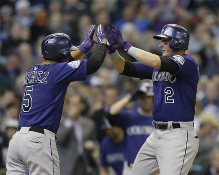 Colorado Rockies' Troy Tulowitzki, right, gets high-fives from Carlos Gonzalez, left, after Tulowitzki's home run in the third inning of an Opening Day baseball game Monday, April 1, 2013, in Milwaukee. (AP Photo/Jeffrey Phelps)