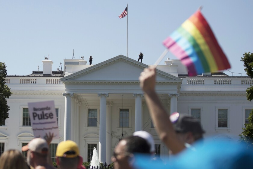 Equality March for Unity and Pride participants march past the White House in Washington.