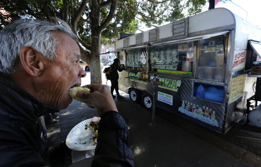 Terril Johnson bites into a taco from the Tacos Ariza food truck in Echo Park, which got a C grade from health inspectors in March but was reinspected and got a B.