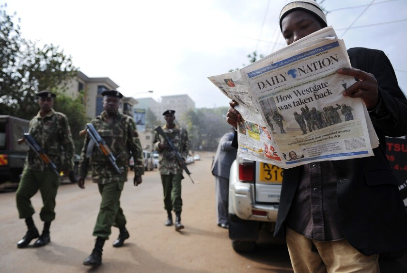 A man reads Wednesday's paper in Nairobi after Kenyan forces took back control of Westgate mall following a days-long siege that killed scores of people.