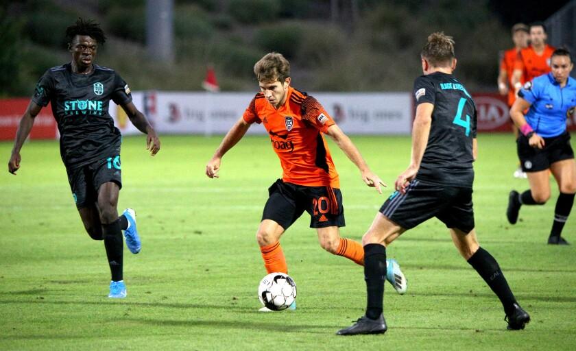 El mediocampista del Orange County Soccer Club, Brian Iloski, regatea entre los defensores en un juego en casa contra los San Diego Loyal.