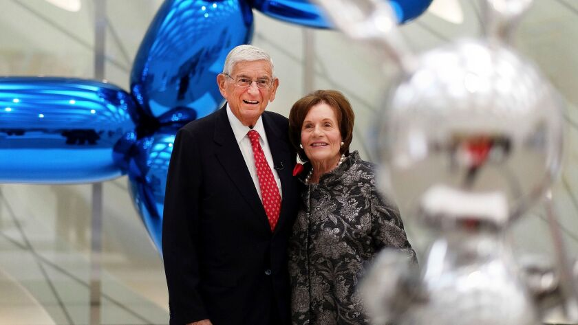 "Billionaire and charter supporter Eli Broad and his wife, Edythe, stand for a photo amid Jeff Koons sculptures at his new museum called ""The Broad"" in downtown Los Angeles."
