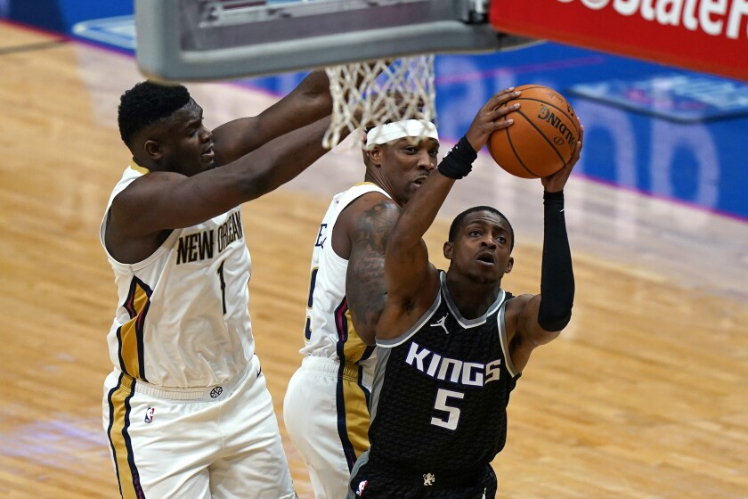 Sacramento Kings guard De'Aaron Fox (5) goes to the basket against New Orleans Pelicans forward Zion Williamson (1) in the first half of an NBA basketball game in New Orleans, Monday, Feb. 1, 2021. (AP Photo/Gerald Herbert)