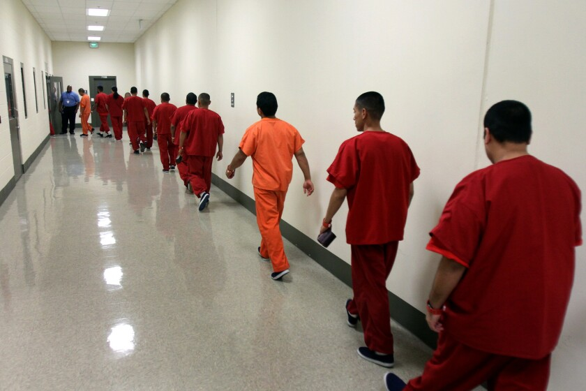 Detainees walk in one of the hallways of a detention facility in Adelanto, Southern California's largest immigrant detention facility.