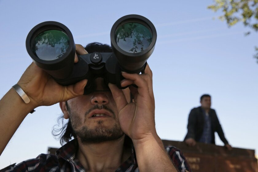 FILE -  In this Monday, Oct. 6, 2014 file photo, a Turkish Kurd, standing on the  the Turkey-Syria border, uses binoculars to watch fighting between militants of the Islamic State group and Kurdish forces in Kobani, Syria, on outskirts of Suruc, Turkey.    The Kurds of Syria and Iraq have become a