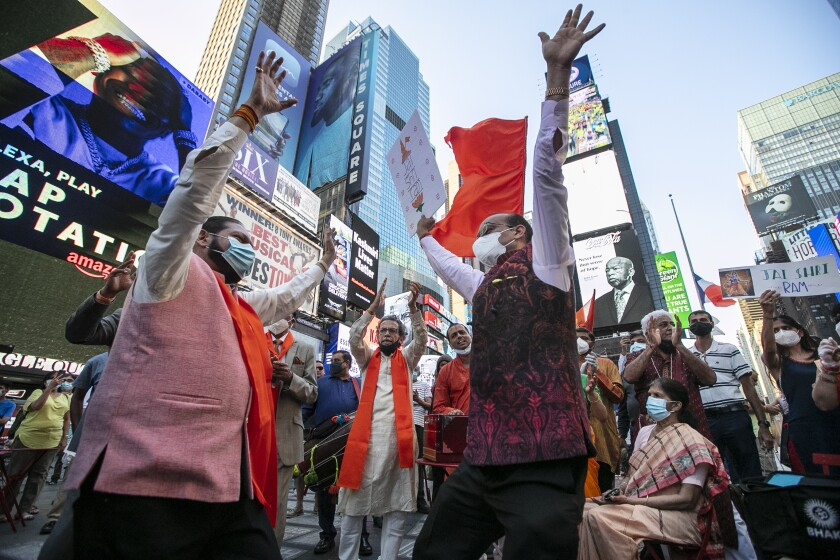People gather in Times Square after the groundbreaking ceremony of a temple dedicated to the Hindu god Ram by Indian Prime Minister Narendra Modi, Wednesday, Aug. 5, 2020, in New York. Hindus rejoiced as Modi broke ground on a long-awaited temple of their most revered god, Ram, at the site of a demolished 16th century mosque. (AP Photo/Frank Franklin II)
