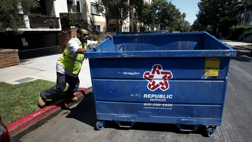 The Los Angeles City Council voted this week to rework its much criticized commercial trash pickup program, known as RecycLA. An employee with Athens Services, one of the program's contractors, moves a trash bin in West Los Angeles in 2017.