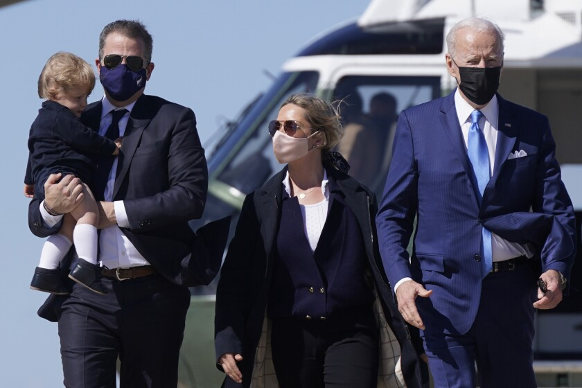 FILE - In this March 26, 2021, file photo President Joe Biden walks with his son Hunter Biden, second from left, as Hunter carries his son Beau and walks next to his wife Melissa Cohen, center, before boarding Air Force One at Andrews Air Force Base, Md. The White House has established an arrangement that would allow President Joe Biden's son Hunter to sell his artwork for tens of thousands of dollars without knowing the identity of the purchaser, an agreement established in attempt to avoid any potential ethical concerns surrounding his sales. (AP Photo/Patrick Semansky, File)