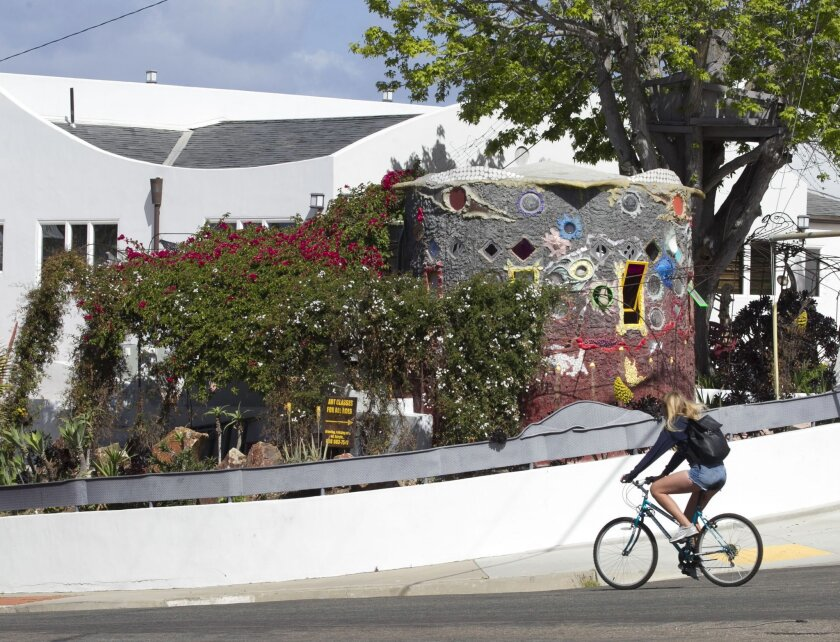 A cyclist On Nautilus Street rides past the artist's yard.