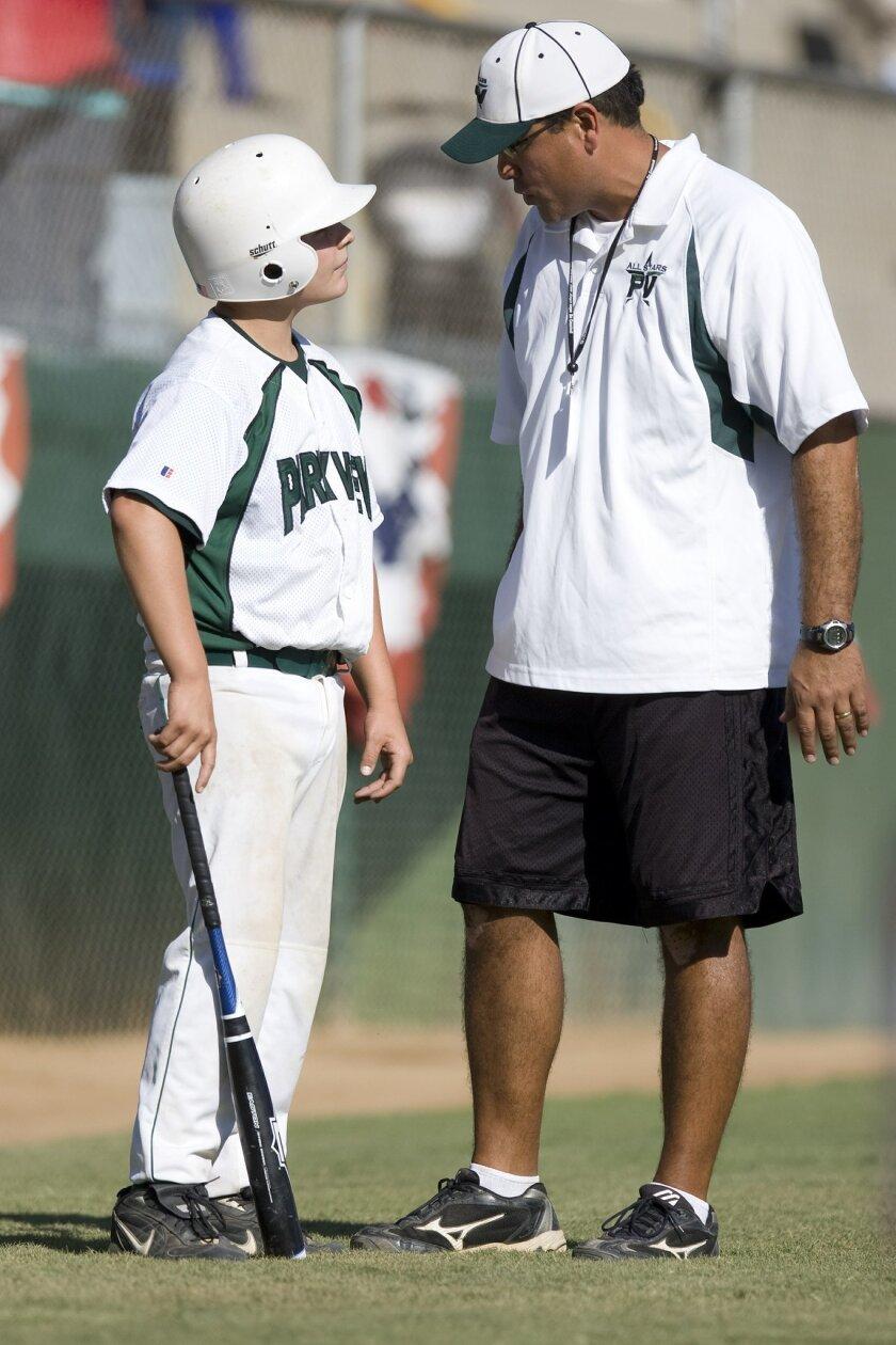 Park View coach Ric Ramirez, who played collegiate ball, talks hitting with Jensen Petersen. (John R. McCutchen / Union-Tribune)