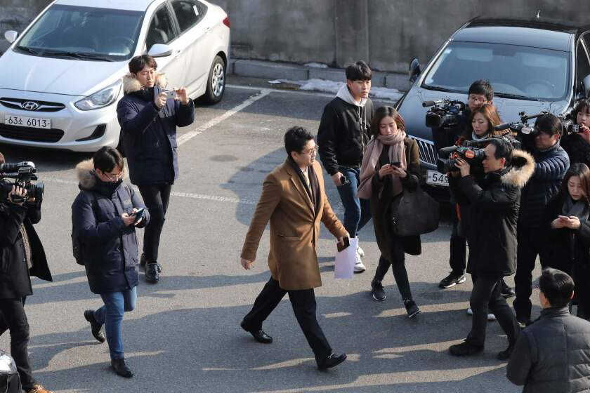 Journalists surround a prosecutor attempting to enter the presidential Blue House in Seoul on Feb. 3, 2017.