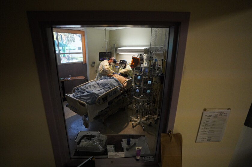 A nurse and respiratory therapist work with a COVID-19 patient at Scripps Mercy Hospital Chula Vista intensive care unit.