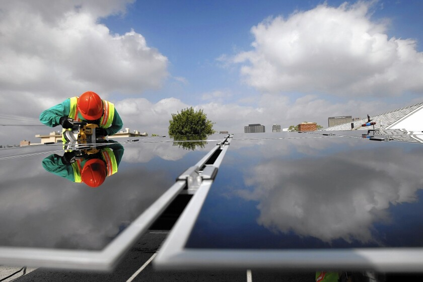 A SolarCity installer puts solar panels on a home in L.A. in 2009.