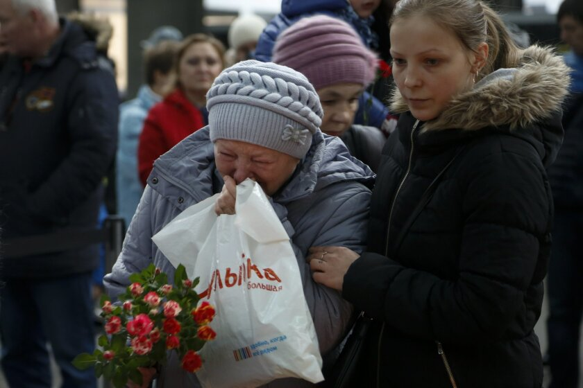 People react as they come to lay flowers and toys at an entrance of Pulkovo airport outside St.Petersburg, Russia, during a day of national mourning for the plane crash victims, on Sunday, Nov. 1, 2015. Hundreds of people are bringing flowers and pictures to St. Petersburg's airport to commemorate