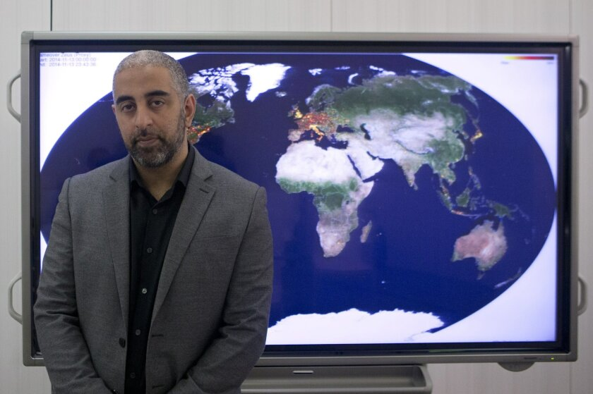 Raj Samani, chief technology officer of Intel Security's Europe, Middle East and Africa division poses for a photograph in front of a screen after speaking during an internet security conference in Madrid, Spain, Thursday, April 9, 2015. A new group of international cybercrime fighters claimed one