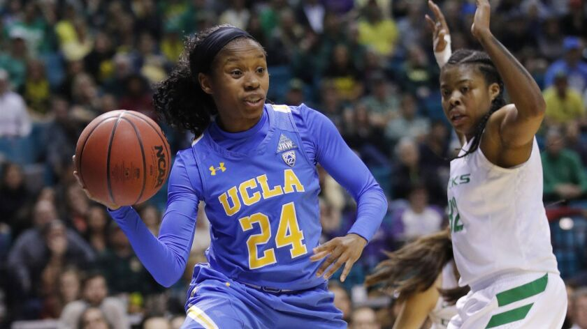 UCLA's Japreece Dean is defended by Oregon's Oti Gildon during the first half of an NCAA college bas