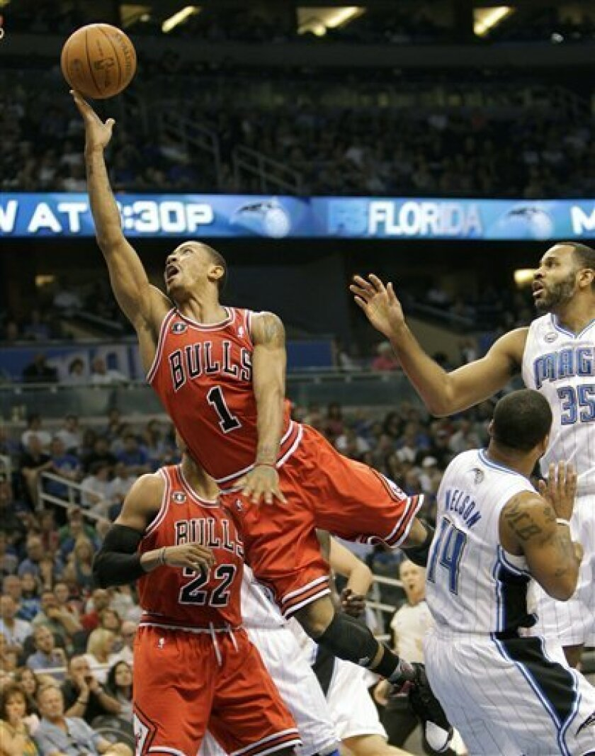 Chicago Bulls' Derrick Rose (1) draws a foul as he goes in for a basket around Orlando Magic's Jameer Nelson (14) during the first half of an NBA basketball game in Orlando, Fla., Sunday, April 10, 2011. (AP Photo/John Raoux)