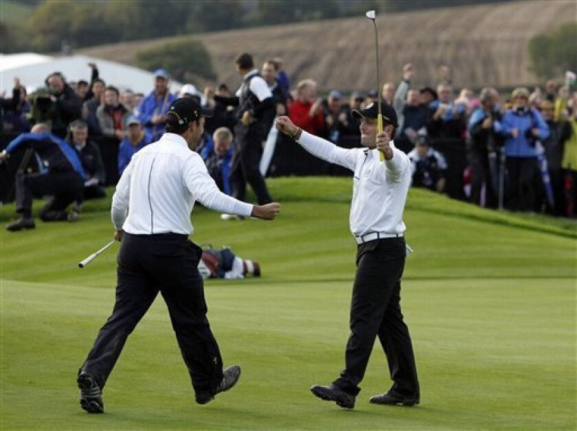 Europe's Francesco, right, and Edoardo Molinari celebrate after securing a half against Stewart Cink and Matt Kuchar of the United States in a foursomes match on the third day of the 2010 Ryder Cup golf tournament at the Celtic Manor Resort in Newport, Wales, Sunday, Oct. 3, 2010. (AP Photo/Jon Super)