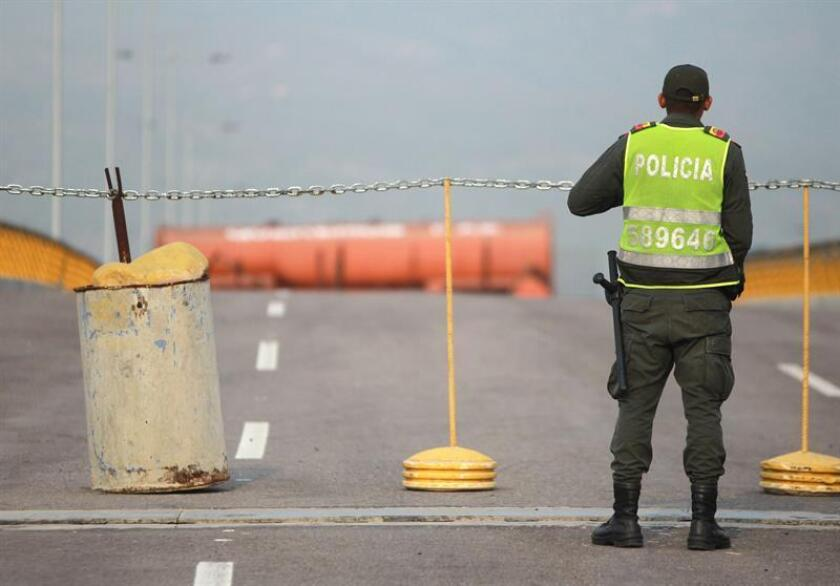 A policeman on Feb. 21, 2019, stands guard on Tienditas Bridge, a border crossing between Colombia and Venezuela, and in sight of an orange tanker trailer, which, along with blue containers welded to the bridge structure, were installed at the beginning of this month by the Nicolas Maduro government to block the bridge and keep humanitarian aid out. EFE-EPA/Ernesto Guzman Jr.