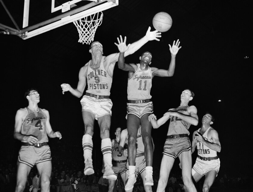 FILE - In this April 1955 file photo, Fort Wayne's Mel Hutchins (9) and Syracuse's Earl Lloyd (11) reach for the ball during an NBA basketball game in Indianapolis. Lloyd, the first black player in NBA history, died Thursday, Feb. 26, 2015. He was 86. Lloyd's alma mater, West Virginia State, confirmed the death. It did not provide details. Lloyd made his NBA debut in 1950 for the Washington Capitals, just before fellow black players Sweetwater Clifton and Chuck Cooper played their first games. (AP Photo/File)