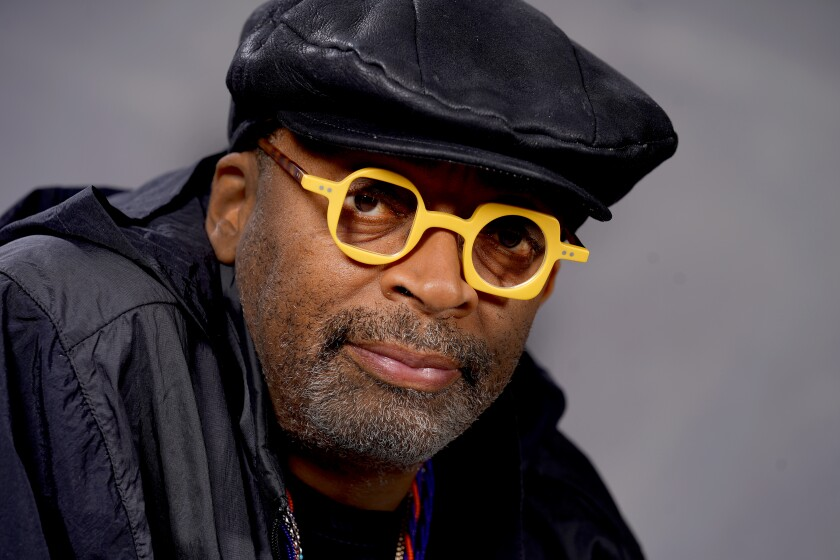 Spike Lee in a black hat and yellow glasses