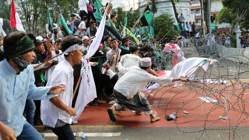 Muslim protesters are confronted by razor wire blocking a road leading to the presidential palace during a rally against Jakarta Gov. Basuki Tjahaja Purnama on Friday.