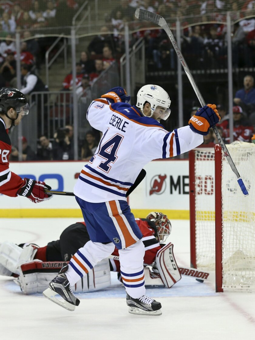 Edmonton Oilers right wing Jordan Eberle celebrates his goal as New Jersey Devils goalie Cory Schneider (35) can't make a stop during the first period of an NHL hockey game Tuesday, Feb. 9, 2016, in Newark, N.J.  (AP Photo/Mel Evans)