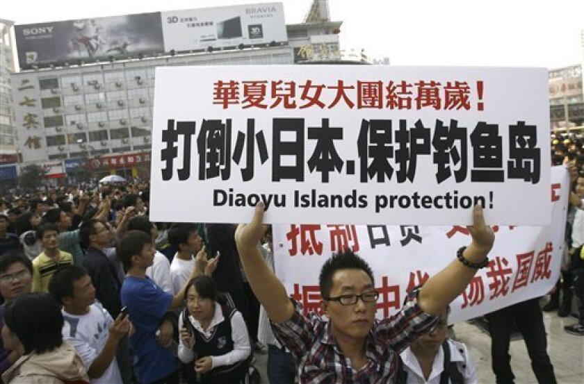 """A man holds a banner while marching during an anti-Japan protest in downtown Zhengzhou, in central China's Henan province, Saturday, Oct. 16, 2010. Chinese characters on the banner reads, """"Down with Japan, Protect Diaoyu Island."""" (AP Photo)"""