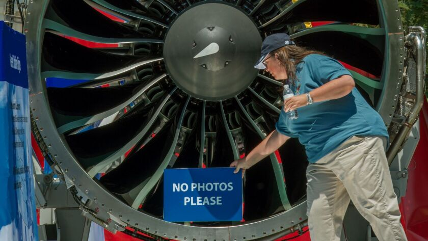 A Pratt & Whitney employee with the company's latest Geared Turbofan engine, seen on display in Wash