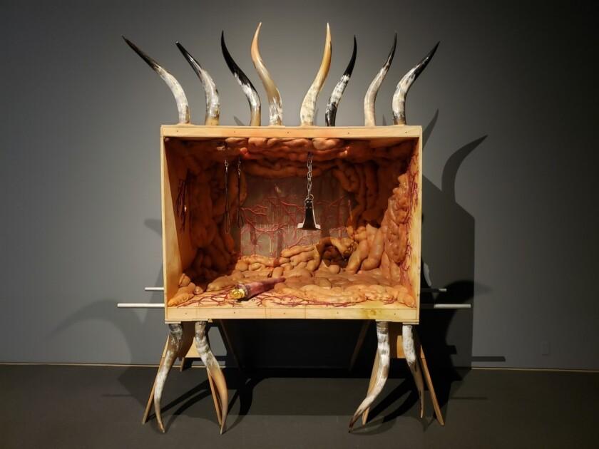 Una caja forrada de intestinos está sostenida por cuernos de animales.  Varios cuernos de animales sobresalen de la punta.