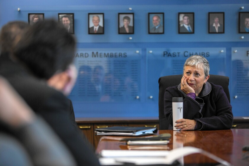 Mary Nichols sits at a table in a room during a meeting with framed photographs of people behind her.