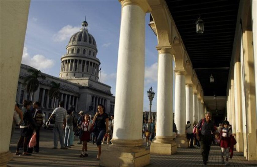 FILE - In this Nov. 24, 2008 file photo, people walk near the Capitol building, background left, in Havana, Cuba. Havana's Capitol building will once again play host to Cuba's parliament for the first time in five decades. City Historian Eusebio Leal said that beginning in 2013, Cuba's parliament w