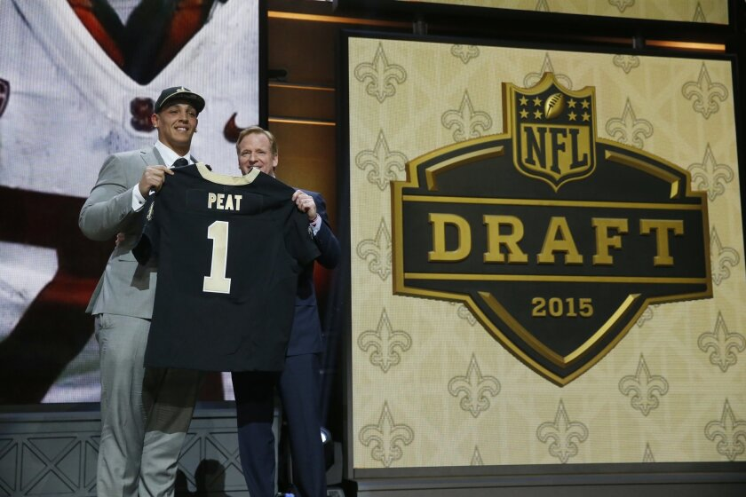 Stanford offensive lineman Andrus Peat poses for photos with NFL commissioner Roger Goodell after being selected by the New Orleans Saints as the 13th pick in the first round of the 2015 NFL Draft,  Thursday, April 30, 2015, in Chicago. (AP Photo/Charles Rex Arbogast)