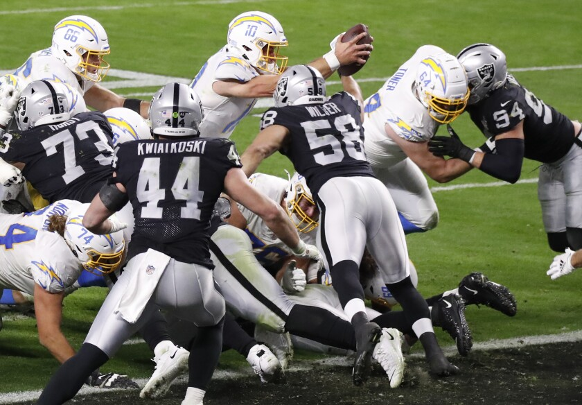Quarterback Justin Herbert of the Los Angeles Chargers dives into the end zone for a touchdown to win the game.