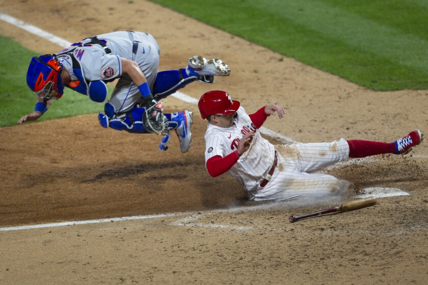 Philadelphia Phillies first baseman Rhys Hoskins (17) scores on an RBI single as New York Mets catcher James McCann (33) goes airborne before he can make the tag during the eighth inning of a baseball game, Monday, April 5, 2021, in Philadelphia. (AP Photo/Laurence Kesterson)