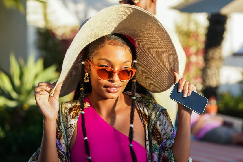 Yara Shahidi wears a big sun hat and sunglasses.