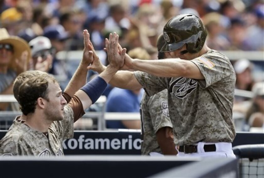 San Diego Padres' Nick Hundley, right, does a two-handed high-five coming back to the dugout after scoring the tying run against the New York Mets in the fifth inning of a baseball game on Sunday, Aug. 18, 2013, in San Diego. (AP Photo/Lenny Ignelzi)