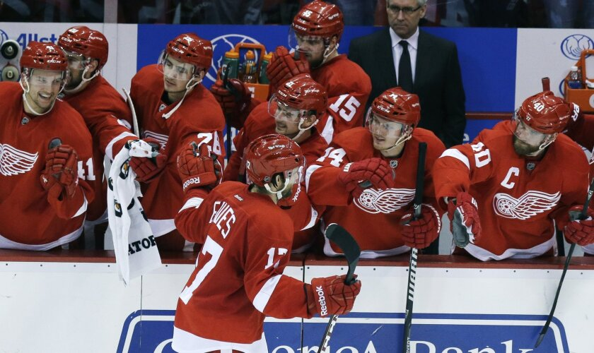 Detroit Red Wings right wing Patrick Eaves (17) is congratulated by teammates after scoring during the shootout of an NHL hockey game against the Washington Capitals in Detroit, Friday, Jan. 31, 2014. The Red Wings won 4-3. (AP Photo/Carlos Osorio)