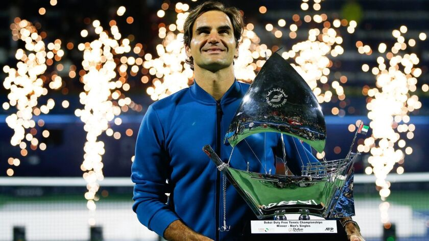Roger Federer of Switzerland poses with the winner's trophy after defeating Stefanos Tsitsipas Dubai Championships on Satuday.