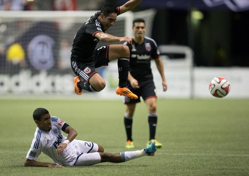 D.C. United's David Estrada, of Mexico, top, leaps to avoid a tackle by Vancouver Whitecaps' Ethen Sampson, lower left, during the first half of an MLS soccer game in Vancouver, British Columbia, on Saturday, Sept. 6, 2014.(AP Photo/The Canadian Press, Darryl Dyck)