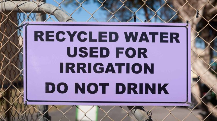 A purple recycled water warning sign attached to a fence