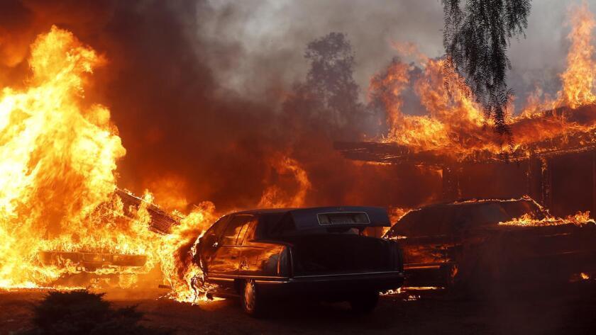 Una casa y autos envueltos en llamas. en el incendio de Creek. (Luis Sinco / Los Angeles Times)