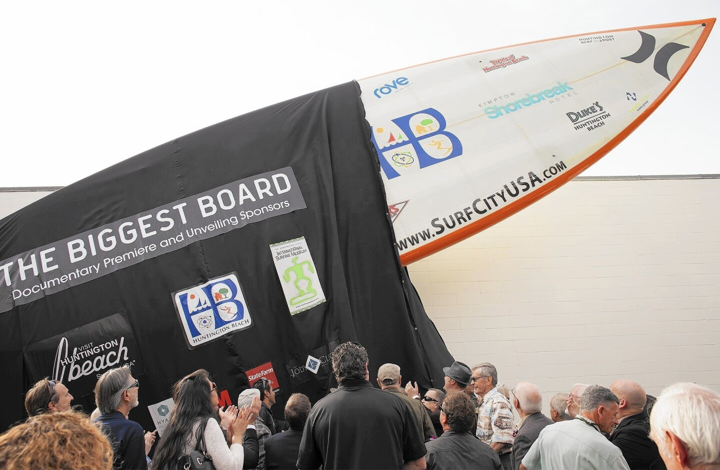 Visit Huntington Beach unveils the world's largest surfboard, 42 1/4 feet long, 11 feet 1 inch wide and 16 inches thick, at the International Surfing Museum in Huntington Beach on Friday, Jan. 22.
