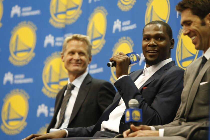 Golden State Warriors' Kevin Durant, center, speaks as coach Steve Kerr, left and general manager Bob Myers listen during a news conference at the NBA basketball team's practice facility, Thursday, July 7, 2016, in Oakland, Calif. (AP Photo/Beck Diefenbach)