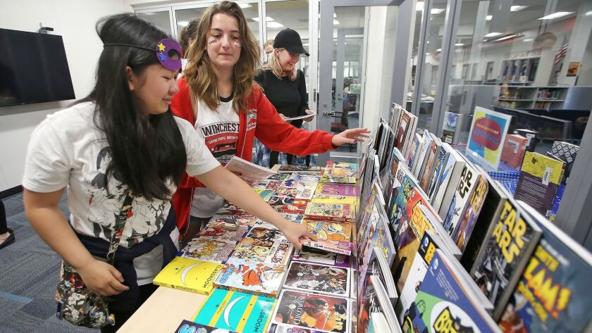 Two friends choose and debate over the best comics on a table during the Laguna Beach Unified School