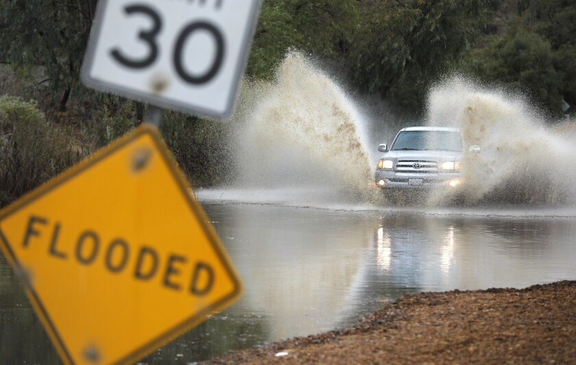 A truck drives through standing water on Hollister Street in the Tijuana River Valley as the first storm of the season moved through the area on Nov. 20, 2019.