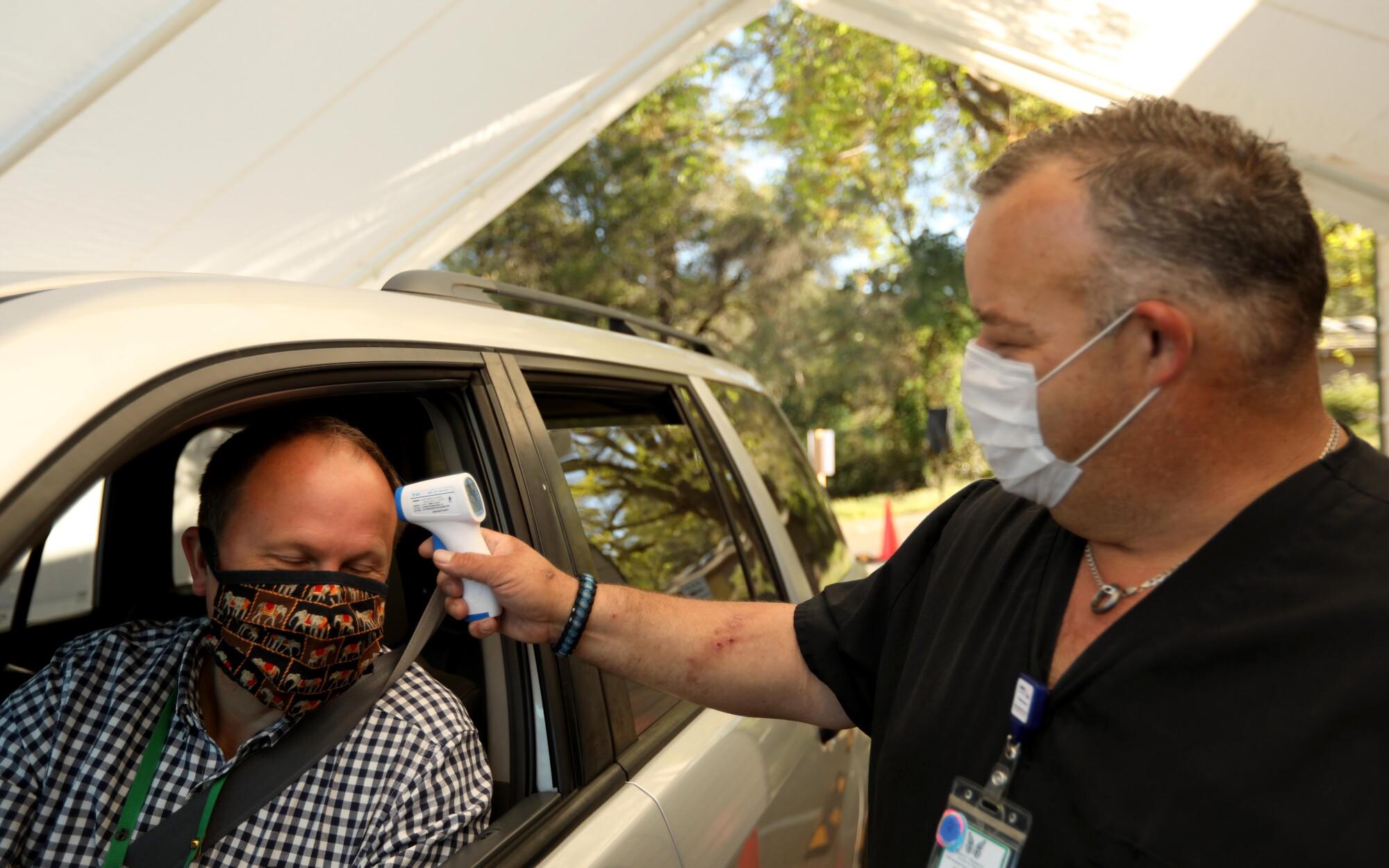 Matthew Matthiessen, CEO of John C. Fremont Hospital, has his temperature taken