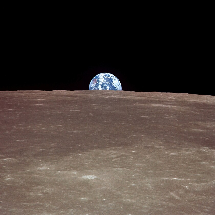 A photo taken during the Apollo 11 mission shows the Earth rising over the moon.
