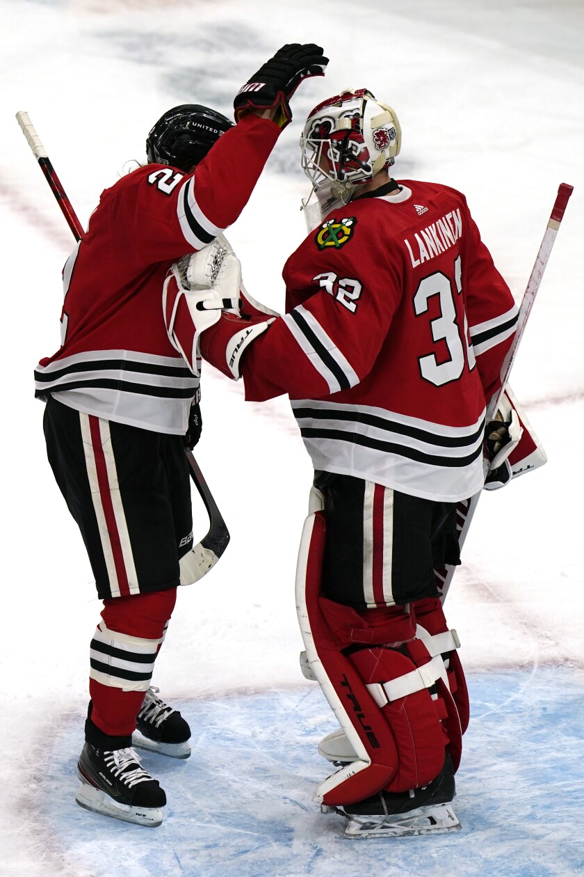 Chicago Blackhawks goalie Kevin Lankinen, right, is congratulated by Duncan Keith after the team's win over the Carolina Hurricanes in an NHL hockey game in Chicago, Thursday, Feb. 4, 2021. (AP Photo/Nam Y. Huh)