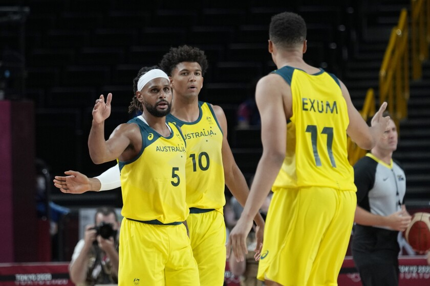 Australia's Patty Mills (5) celebrates a play with teammates Matisse Thybulle (10) and Dante Exum (11) during a men's basketball preliminary round game at the 2020 Summer Olympics, Sunday, July 25, 2021, in Saitama, Japan. (AP Photo/Eric Gay)